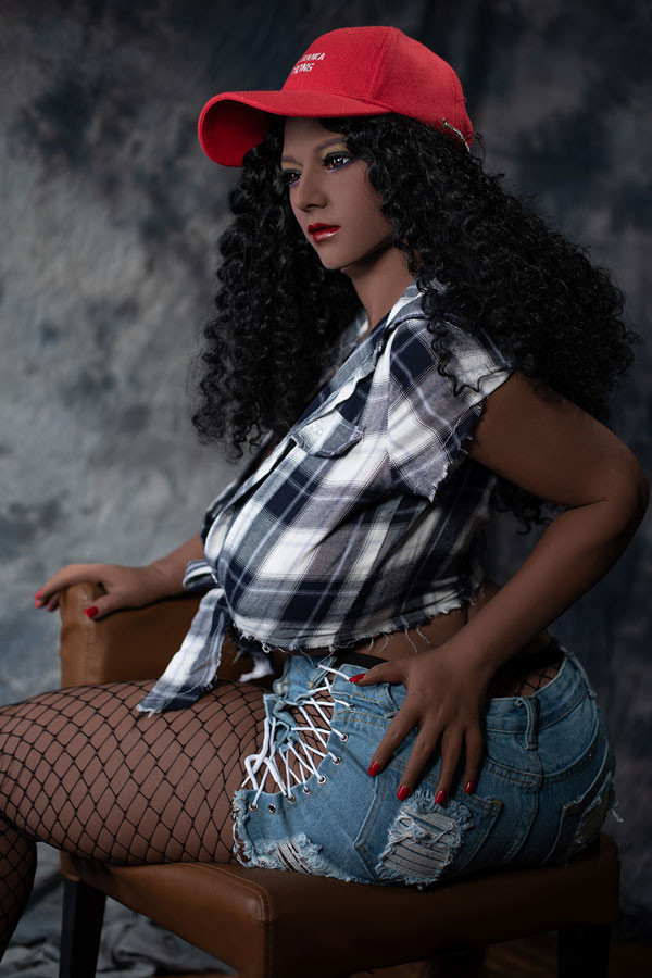 A black sex doll sitting upside down on a chair and touching her ass