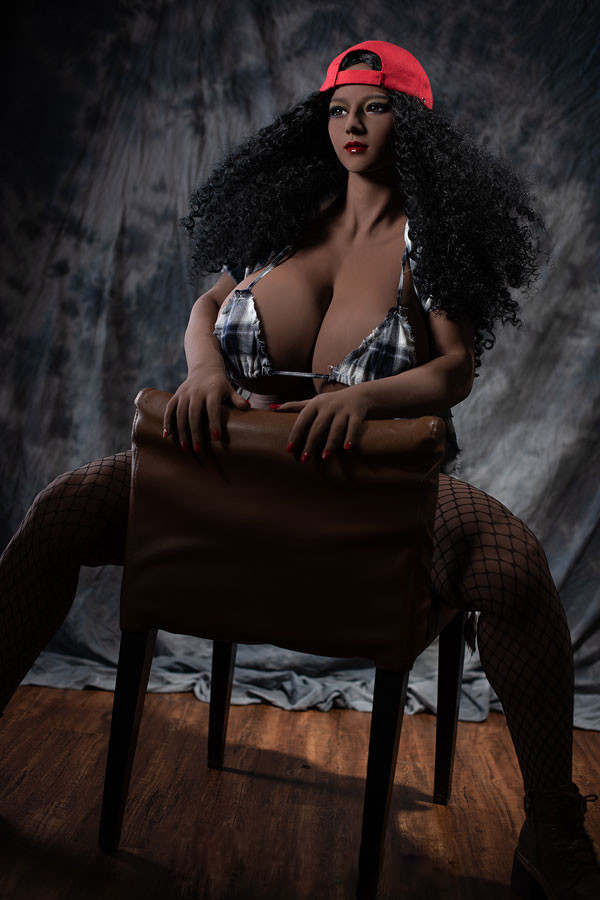 Black sex doll sitting upside down on a chair