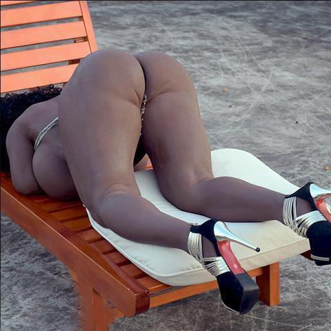 Black sex doll with legs kneeling on a chair